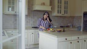 Толстенькая девушка варит в кухне акции видеоматериалы