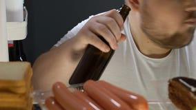 Толстенькая пивная бутылка отверстия холостяка от холодильника и выпивать, нездоровое питание видеоматериал
