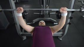 Толстенький мужчина поднимаясь вверх по штанге едва ли заканчивая комплект, желание быть сильный и тонкий акции видеоматериалы