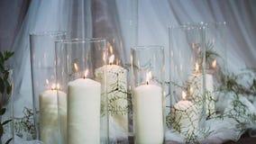 Толстые горящие свечи стоя в прозрачных вазах окруженных тканями сток-видео