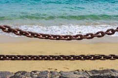 Толстые ржавые цепи с морем на заднем плане стоковое фото