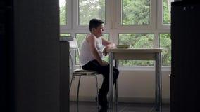 Толстый мальчик сидит в кухне на таблице смотря еду плиты на предпосылке окна акции видеоматериалы