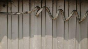 Толстый пакостный спиральный электрический провод на рифлёной стальной стене стоковая фотография