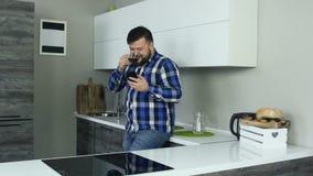 Толстый человек стоит в кухне и смехе, смотря телефон, тогда глоточки глоточек кофе Жирный парень в видеоматериал