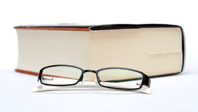 Толщиные книга и стекла Стоковые Изображения