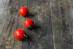 3 томата вишни на старом деревянном столе Стоковая Фотография
