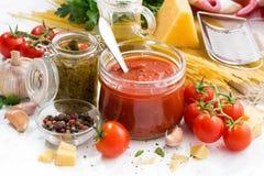Томатный соус, pesto и ингридиенты для макаронных изделий на белой таблице стоковые изображения