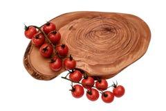 Томаты вишни лежат на деревянной доске пересыхающее маслоо, изолированной на белой предпосылке Стоковое Изображение