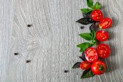 Томаты вишни и свежий базилик на серой деревянной предпосылке Рамка скопируйте космос Стоковая Фотография RF