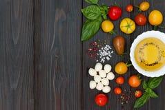 Томаты вишни, моццарелла, листья базилика, специи и оливковое масло сверху Итальянские caprese ингридиенты рецепта салата Стоковая Фотография