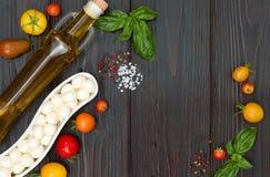 Томаты вишни, моццарелла, листья базилика, специи и оливковое масло сверху Итальянские caprese ингридиенты рецепта салата Стоковые Фотографии RF