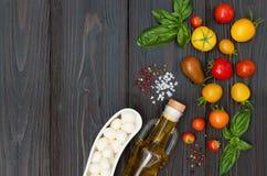 Томаты вишни, моццарелла, листья базилика, специи и оливковое масло сверху Итальянские caprese ингридиенты рецепта салата Стоковые Изображения RF