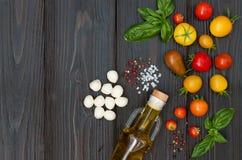 Томаты вишни, моццарелла, листья базилика, специи и оливковое масло сверху Итальянские caprese ингридиенты рецепта салата Стоковое фото RF