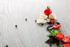 Томаты вишни, чеснок и свежий базилик на серой деревянной предпосылке Рамка скопируйте космос Стоковая Фотография RF