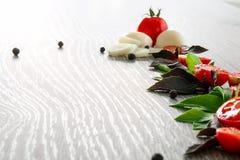 Томаты вишни, чеснок и свежий базилик на серой деревянной предпосылке Рамка скопируйте космос Стоковые Фотографии RF