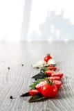 Томаты вишни, чеснок и свежий базилик на серой деревянной предпосылке Рамка скопируйте космос Стоковая Фотография
