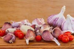 Томаты вишни, чеснок на винтажной деревянной таблице - Стоковое Изображение