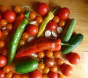 Томаты, вишня, огурцы, чеснок и перцы - vegetable предпосылка Стоковые Фотографии RF