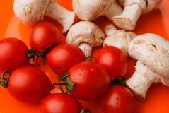 Томаты и грибы вишни на оранжевой предпосылке Стоковое Фото