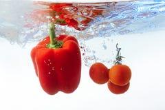Томаты и перец вишни в изолированной воде Стоковые Фотографии RF