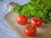 Томаты и салат на деревянной предпосылке Стоковые Изображения RF
