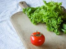 Томаты и салат на деревянной предпосылке Стоковая Фотография
