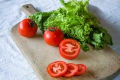 Томаты и салат на деревянной предпосылке Стоковое Изображение