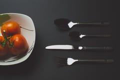 томаты и столовый прибор Стоковое Фото