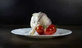 Томаты и чеснок в белой плите Стоковое фото RF