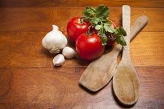 Томаты и чеснок с деревянными ложками Стоковое Изображение RF