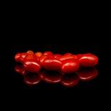 Томаты младенца, томаты вишни и вода падают на черную предпосылку с отражением Стоковая Фотография