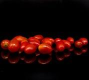 Томаты младенца, томаты вишни и вода падают на черную предпосылку с отражением Стоковые Изображения