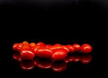 Томаты младенца, томаты вишни и вода падают на черную предпосылку с отражением Стоковая Фотография RF