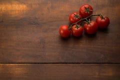 Томаты на коричневой текстурированной древесине Стоковое фото RF