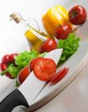 томаты ножа действия керамические прерывая белые стоковое фото rf