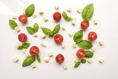 Томаты, сыр, базилик на белой предпосылке томат салями пиццы paprica ингридиентов сыра Стоковое фото RF