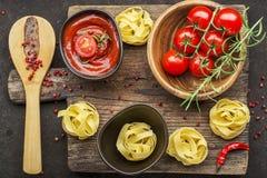 Томаты, томатный соус, макаронные изделия, розмариновое масло, красный пеец для варить блюда на темной предпосылке Взгляд сверху Стоковое фото RF
