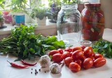 Томаты, чеснок и специи на таблице Подготовка посоленного томата домашняя консервация стоковые изображения