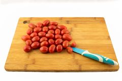 Томат вишни на деревянной доске с ножом и белой предпосылкой Стоковое Изображение RF