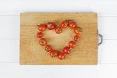 Томат еды сердца влюбленности Стоковые Изображения