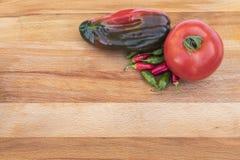 Томат и перцы на разделочной доске Стоковая Фотография RF