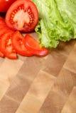 Томат и салат на прерывая доске Стоковые Изображения