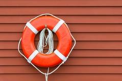 Томбуй кольца на красной деревянной стене Стоковая Фотография
