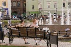 Томск, Россия, улица Ленина 10-ое июля 2017 Идти на улицы города в лете 2 люд сидят на стенде Стоковые Изображения