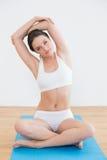 Тонизированная женщина протягивая в студии фитнеса Стоковые Изображения RF