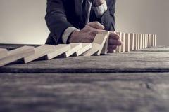 Тонизированное изображение бизнесмена останавливая эффект домино Стоковые Фотографии RF