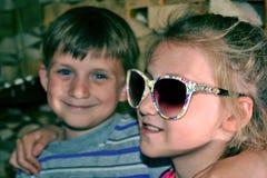 Тонизированное изображение девушки в солнечных очках, обнимает ее младший брата Стоковое Фото