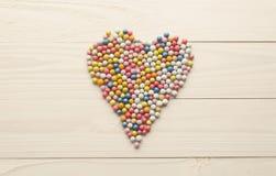 Тонизированное изображение красочных круглых конфет лежа в форме сердца дальше Стоковая Фотография