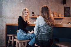 Тонизированное изображение лучших другов имея дату в кафе или ресторане Красивые девушки говоря или связывая пока выпивающ Стоковое Изображение RF