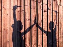 Тонизированное изображение силуэтов людей и женщин держа руки с ракетками тенниса Стоковая Фотография RF